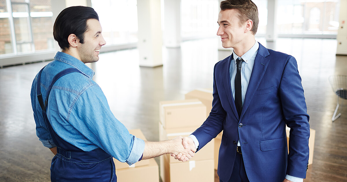 Business owner and removalist shake hands after corporate moving