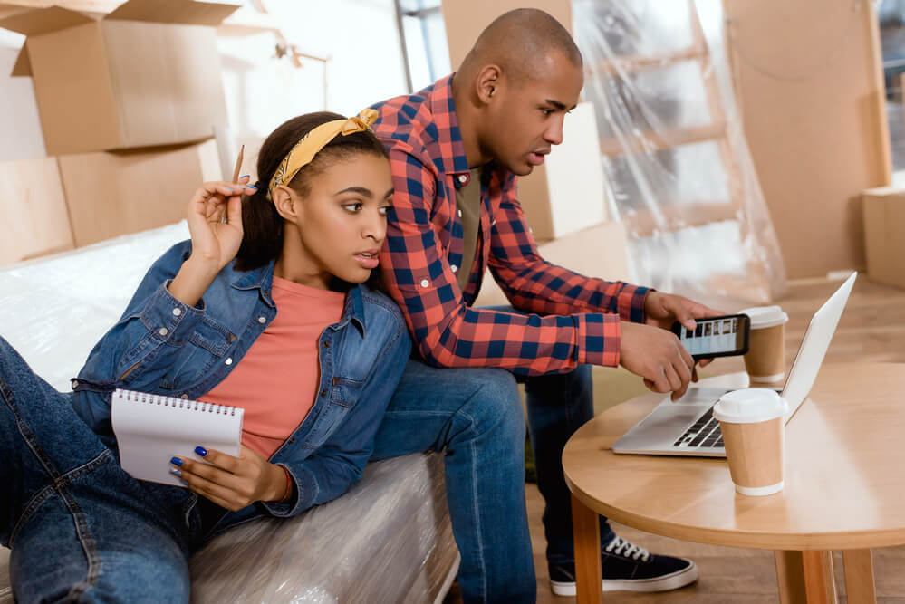 couple-planning-to-move-with-notepad-and-laptop