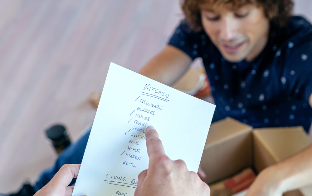 A young couple using a list to help guide them through removals