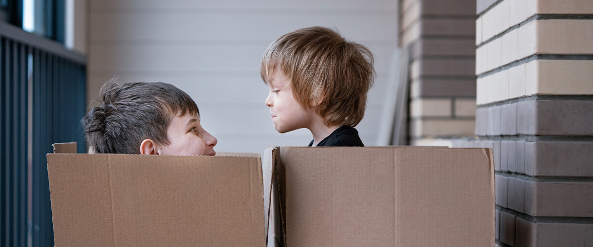 Two young kids sitting in boxes playing waiting for their interstate move