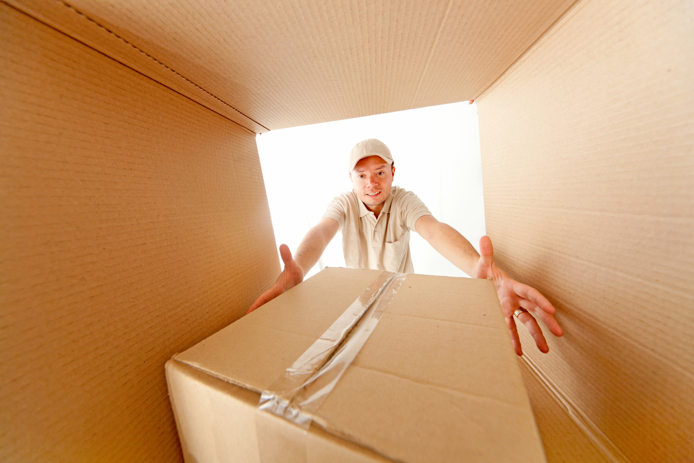 Moving man grabbing a package from inside a box
