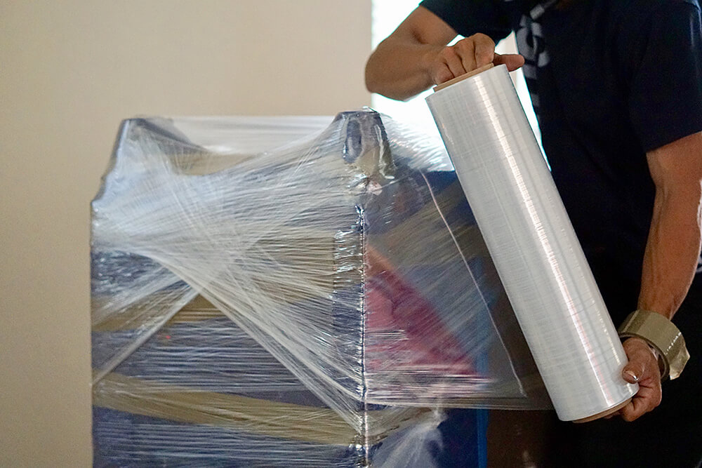 furniture being wrapped in plastic before storage