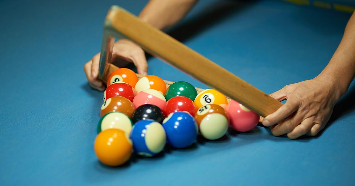 Setting up billiard balls on pool table